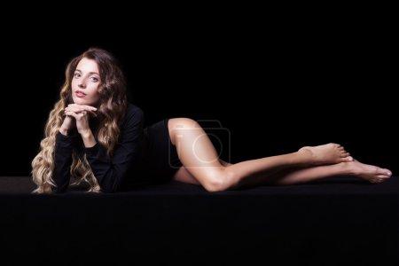Portrait of beautiful caucasian model posing on black cloth on b