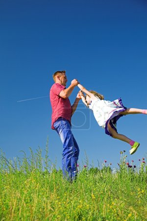 Photo for Happy family rest on the summer meadow, father fun throws up daughter in the air. - Royalty Free Image