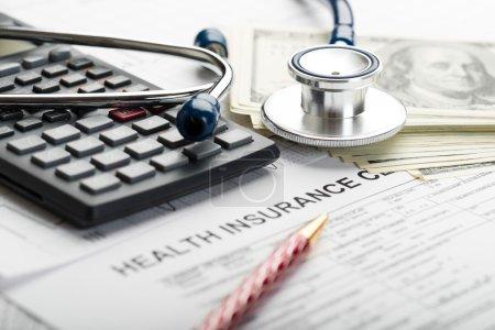 Photo pour Stéthoscope, calculatrice, stylo bille et billets en dollars sur le formulaire de demande de règlement d'assurance maladie close-up - image libre de droit