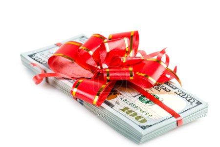 Photo pour Cadeau d'argent, grosse pile de dollars avec arc rouge isolé sur fond blanc - image libre de droit
