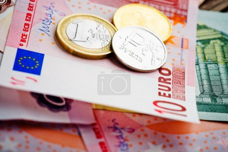 Euro and ruble coins on euro banknotes