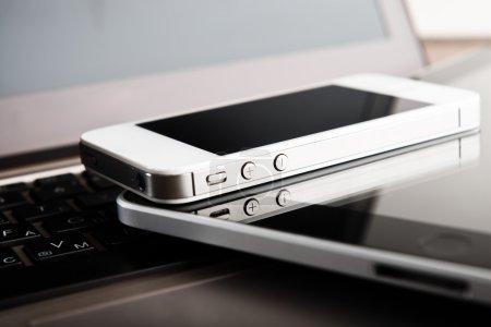 Photo pour Deux téléphones et tablette PC sur ordinateur portable - image libre de droit