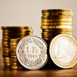 One euro coin and one swiss frank and gold money o...