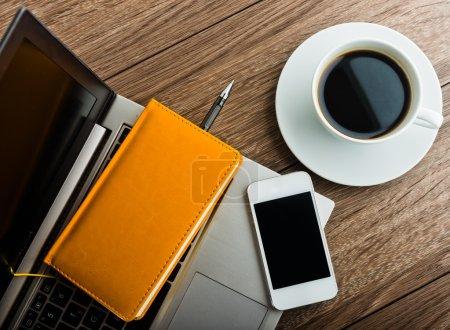 Foto de Escritorio de oficina con ordenador portátil, planificador, móvil smartphone y taza de café - Imagen libre de derechos