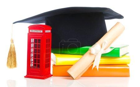 Photo pour Education in Great Britain Concept. Empilement de livres, mortier, diplôme et cabine téléphonique rouge - symbole de l'Angleterre - image libre de droit