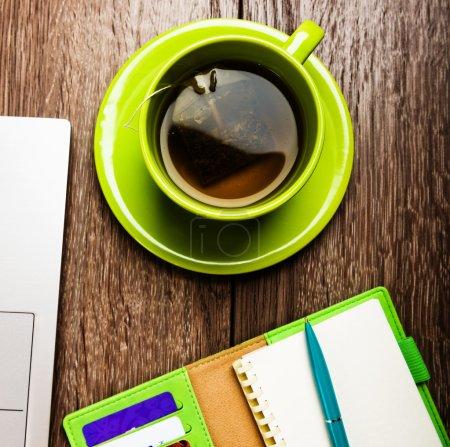 Foto de Escritorio de oficina con computadora portátil, planificador, taza de camiseta - Imagen libre de derechos