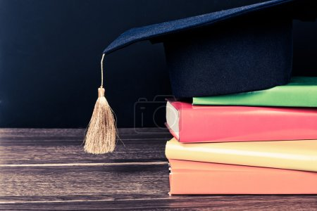 Graduation mortarboard on books