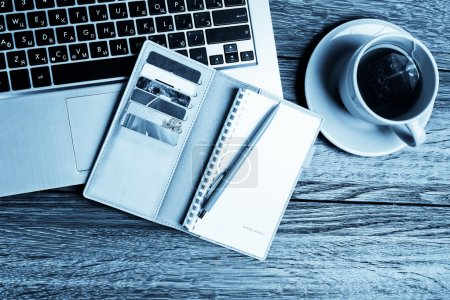 Foto de Escritorio de oficina con computadora portátil, planificador, taza de té. Tono azul - Imagen libre de derechos