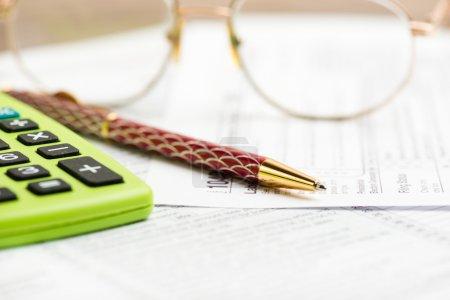 Photo pour Poste de travail d'entreprise avec les formalités de déclaration de revenus, la calculatrice et stylo et dollar - image libre de droit