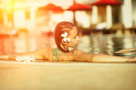 Photo pour Fille dans la piscine tropicale avec fleur dans les cheveux - image libre de droit