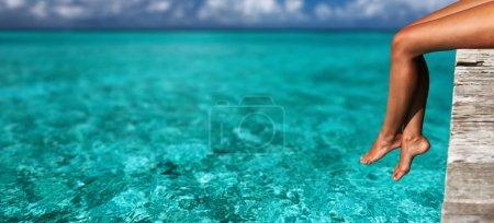 Photo pour Jambes de femme relaxantes à la jetée de la plage - image libre de droit