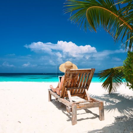 Photo for Rear view of young woman in hat sitting on chaise-lounge with tablet pc at the beach - Royalty Free Image