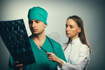 Photo pour Équipe des médecins avec portrait spinal scan IRM sur fond gris - image libre de droit