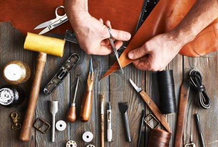 Photo pour Homme travaillant avec cuir artisanat bricolage outils - image libre de droit