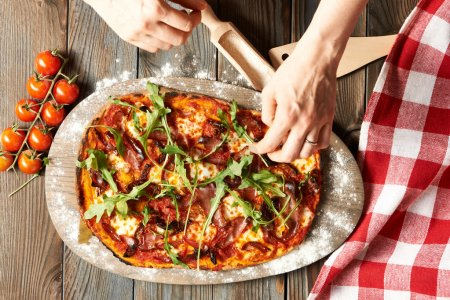 Photo for Female hands with Home made pizza on wooden rustic table - Royalty Free Image
