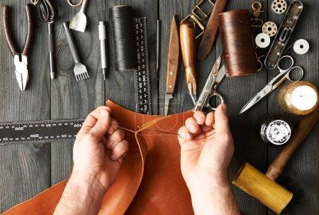 Photo pour Homme travaillant avec du cuir en utilisant des outils de bricolage - image libre de droit