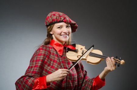 Photo for Woman in scottish clothing in musical concept - Royalty Free Image