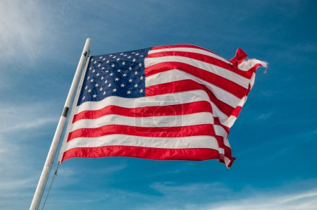 Photo for American flag against bright blue sky - Royalty Free Image