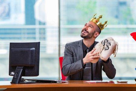 Photo pour Homme d'affaires avec couronne et sacs d'argent dans le bureau - image libre de droit