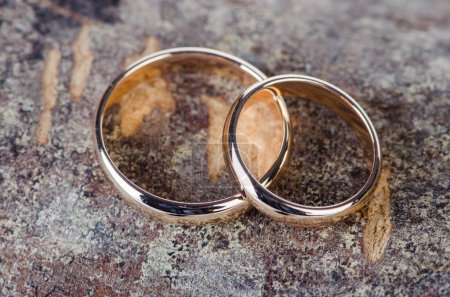 Two gold wedding rings on wooden background