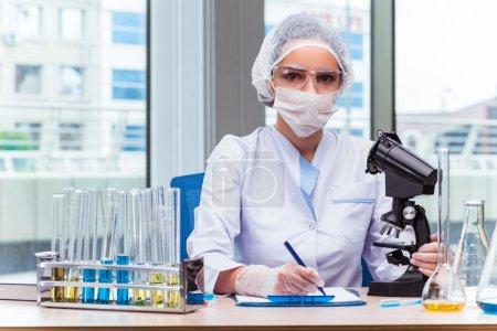 Photo pour Jeune étudiant travaillant avec des solutions chimiques en laboratoire - image libre de droit