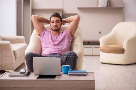 Photo pour Jeune employé de sexe masculin travaillant à domicile pendant la pandémie - image libre de droit