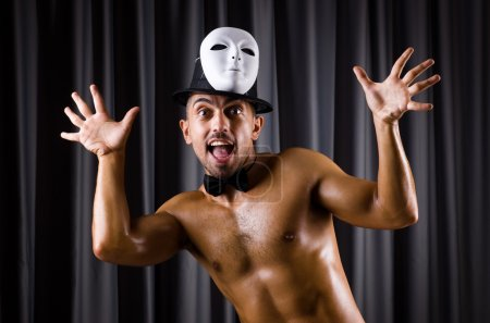 Muscular actor with theatrical mask