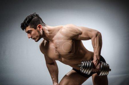 Photo pour Bodybuilder déchiré musculaire avec haltères - image libre de droit