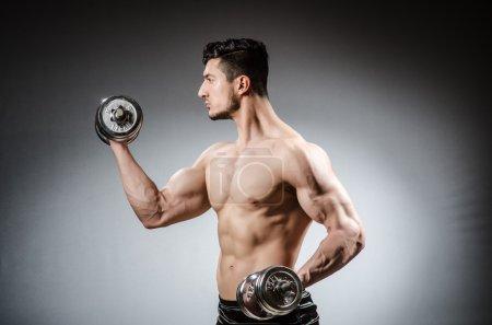 Muscular man posing on grey background