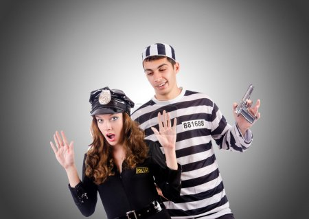Police lady and prison inmate with gun against gre...