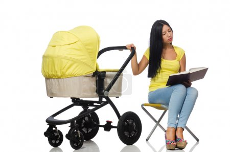 Young mom with baby and pram reading book