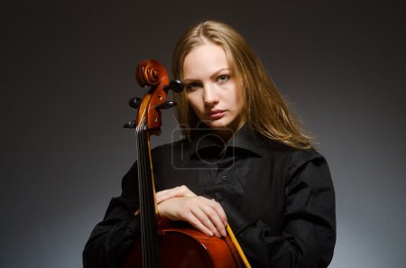 Photo for Woman playing classical cello in music concept over dark grey - Royalty Free Image