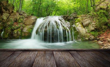 Photo pour Cascade de forêt et rochers couverts de mousse et jetée de bois - image libre de droit