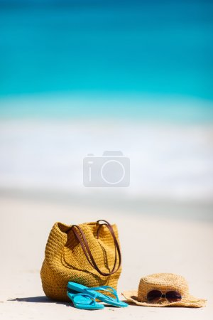 Photo for Straw bag, sun glasses, towel and flip flops on a tropical beach - Royalty Free Image