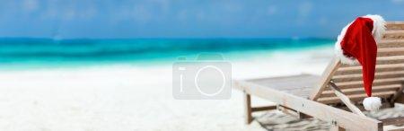 Photo pour Panorama de chaises longues avec chapeau de Père Noël à la belle plage tropicale avec sable blanc et eau turquoise, vacances de Noël parfaites - image libre de droit