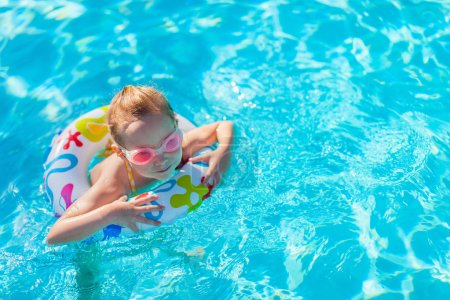 Photo for Adorable little girl at swimming pool having fun during summer vacation - Royalty Free Image