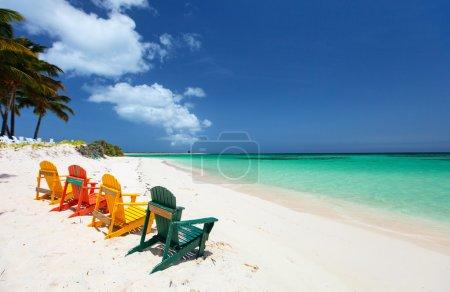 Photo pour Rangée des chaises en bois colorés à la plage de sable blanc tropicale dans les Caraïbes - image libre de droit