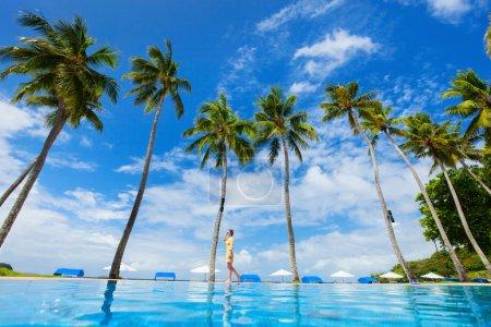 Photo pour Jeune belle femme marchant le long de la piscine à débordement à la plage tropicale avec palmiers - image libre de droit