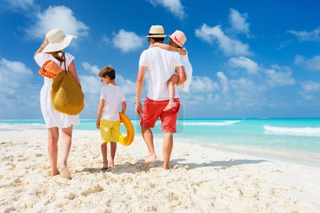 Photo for Back view of a happy family at tropical beach on summer vacation - Royalty Free Image