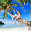 Mother and little girl at tropical beach sitting o...