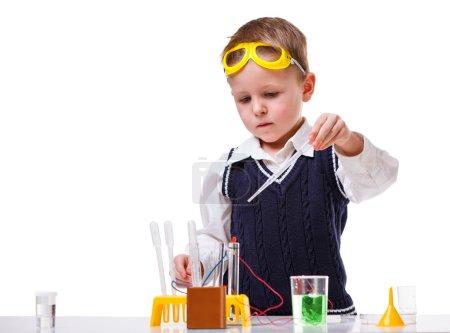 Foto de Niño realizando experimentos de química con diferentes líquidos . - Imagen libre de derechos