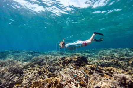 Photo pour Photo sous-marine de femme plongée libre et tuba dans une eau tropicale claire au récif corallien - image libre de droit