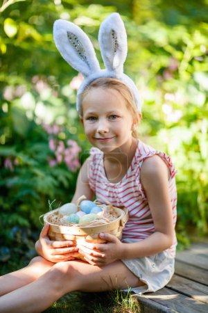 Photo pour Adorable petite fille portant des oreilles de lapin tenant un panier avec des œufs de Pâques à l'extérieur le jour du printemps - image libre de droit