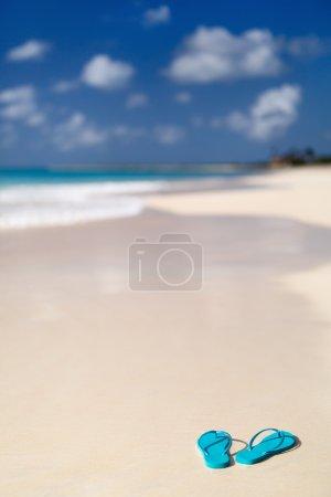 Photo pour Tongs turquoise sur une plage tropicale - image libre de droit