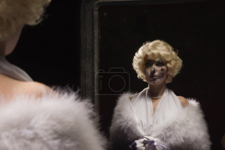 Woman with make-up skeleton looks at himself in the mirror