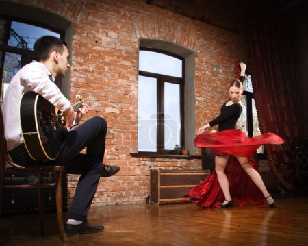 Photo for Young woman dancing flamenco in traditional flamenco dress with fan and a man playing the guitar - Royalty Free Image