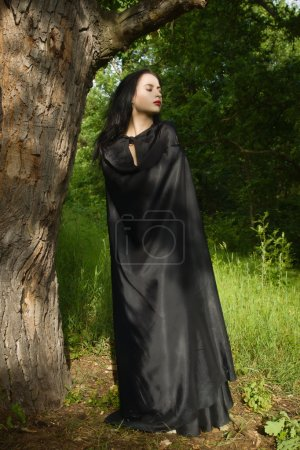 Beautiful brunette woman in black dress and black cloak in the m