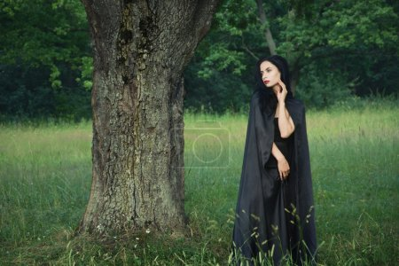 Beautiful brunette woman in black dress and black cloak