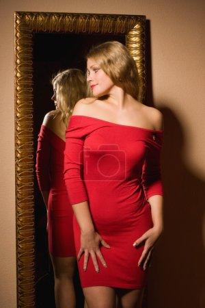 Foto de Mujer de moda en un vestido rojo mirando su reflejo en mirro - Imagen libre de derechos