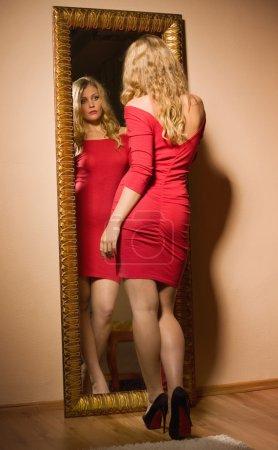 Foto de Fashionable lady in a red dress looking at her reflection in mirror - Imagen libre de derechos